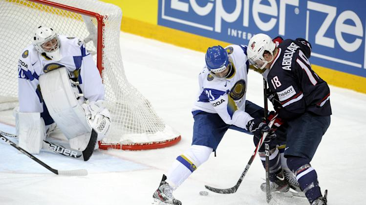 Kazakhstan's goalie Vitali Kolesnik, left, observes while Dmitri Dudarev of Kazakhstan and USA's Justin Abdelkader fight for the puck during the Group H preliminary game Kazakhstan vs USA in the 2012 IIHF Ice Hockey World Championships in Helsinki, Finland, Friday  May 11, 2012. (AP Photo / Vesa Moilanen, Lehtikuva) FINLAND OUT