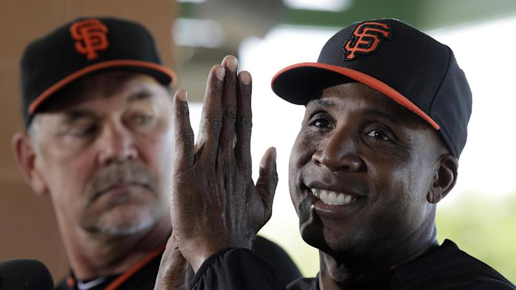 San Francisco Giants manager Bruce Bochy, left, listens as former player Barry Bonds speaks at a news conference before a spring training baseball game in Scottsdale, Ariz., Monday, March 10, 2014. Bonds starts a seven day coaching stint today. (AP Photo/Chris Carlson)