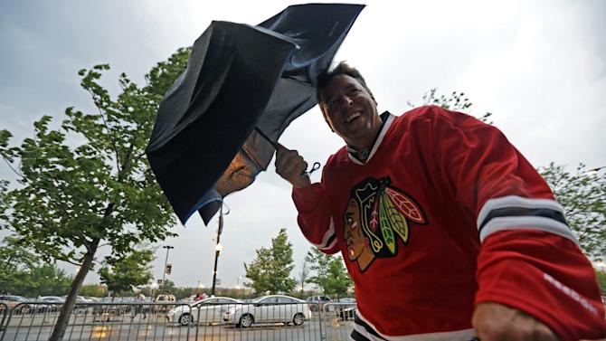 Fans arrive at the United Center in the stormy weather for Game 1 of the NHL Stanley Cup Final hockey series between the Chicago Blackhawks and the Boston Bruins, Wednesday, June 12, 2013, in Chicago. (AP Photo/Nam Y. Huh)