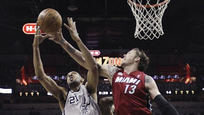 San Antonio Spurs' Tim Duncan (21) and Miami Heat's Mike Miller (13) reach for a rebound during the first half of an NBA basketball game, Sunday, March 31, 2013, in San Antonio. (AP Photo/Eric Gay)