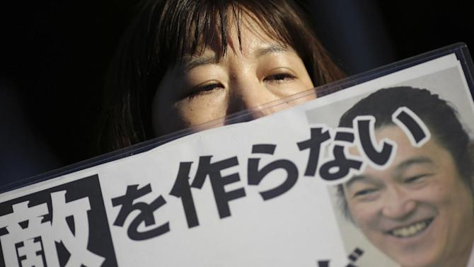 "A woman sympathizer for Japanese hostage Kenji Goto holds a sign stating: ""Do not make an enemy"" and bearing his photo in front of the prime minister's official residence in Tokyo Sunday, Feb. 1, 2015 after an online video purporting to show an Islamic State group militant beheading Goto was circulated via social media. Appalled and saddened by news of journalist Goto's beheading, Japan ordered heightened security precautions, but vowed not to give in to terrorism. (AP Photo/Eugene Hoshiko)"