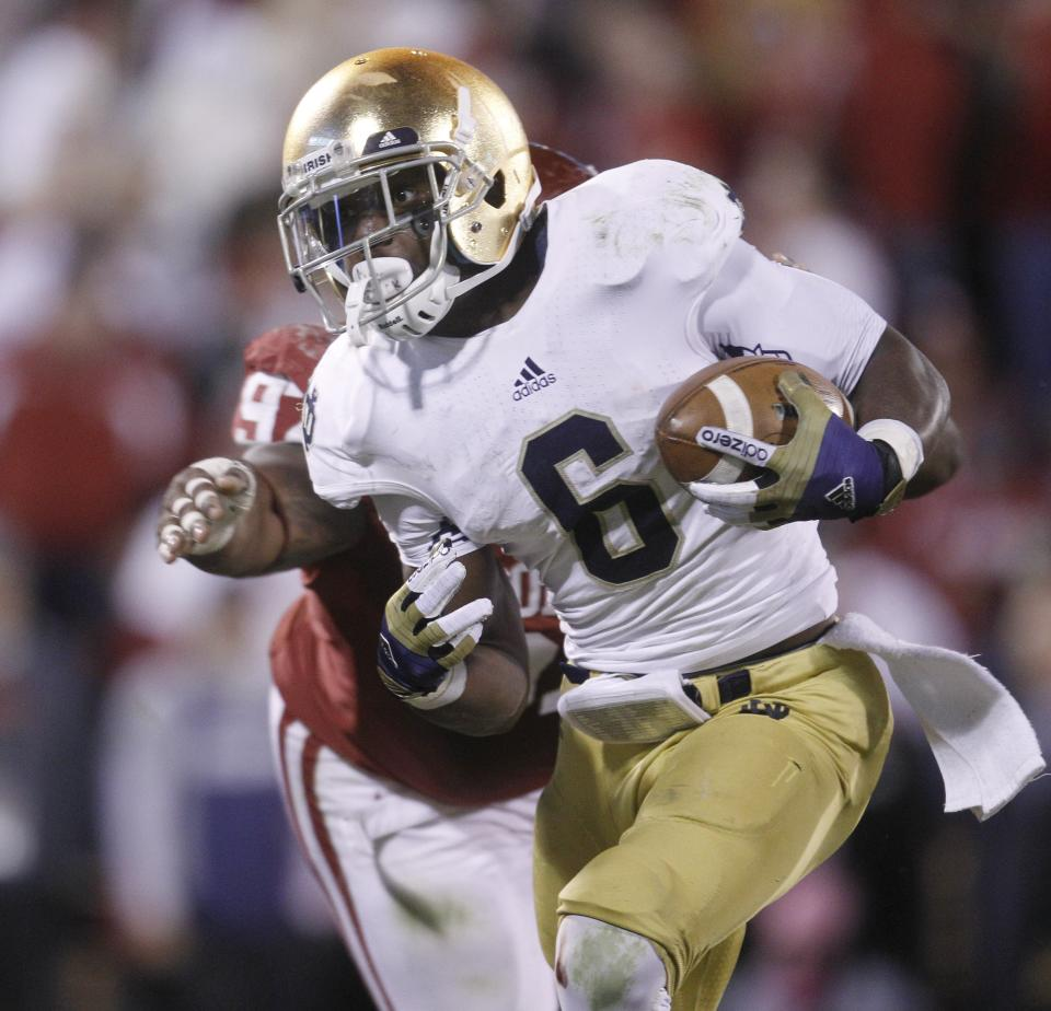 Notre Dame running back Theo Riddick carries past Oklahoma defensive tackle Jamarkus McFarland, rear, on his touchdown run in the fourth quarter of an NCAA college football game in Norman, Okla., Saturday, Oct. 27, 2012. Notre Dame won 30-13. (AP Photo/Sue Ogrocki)