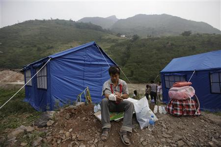 A injured survivor adjusts his bandages in front of tents in Luozehe town after two earthquakes hit Yiliang, Yunnan province September 8, 2012.