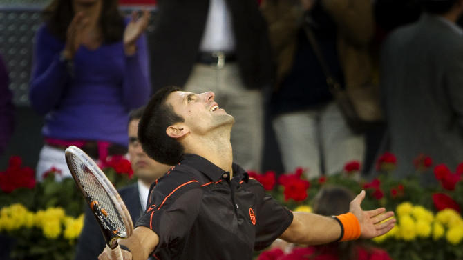 Novak Djokovic from Serbia celebrates after defeating Rafael Nadal from Spain following their singles final tennis match during the Madrid Open tennis tournament in Madrid, Sunday, May 8, 2011. (AP Photo/Arturo Rodriguez)