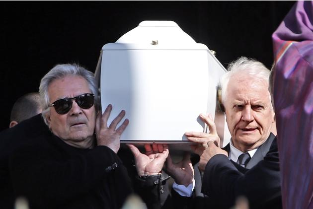 French actors Pierre Arditi and Andre Dussollier carry the coffin of late film director Alain Resnais after his funeral ceremony at the Saint-Vincent-de-Paul church in Paris