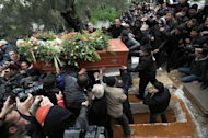 Tunisians carry the coffin of assassinated opposition leader Chokri Belaid during his burial at El-Jellaz cemetery in a suburb of Tunis on February 8, 2013