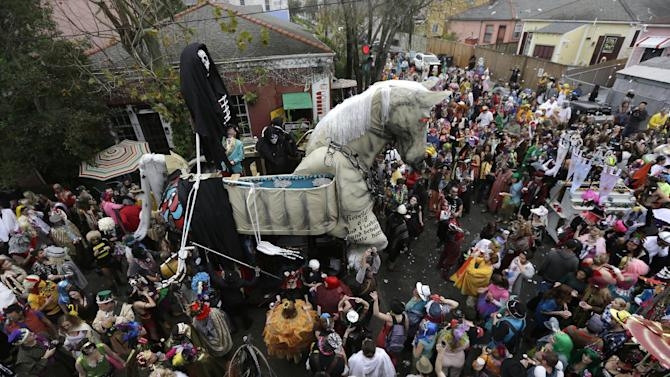 A trojan horse float makes its way through the crowd as revelers gather for the start of the Society of Saint Anne walking parade in the Bywater section of New Orleans during Mardi Gras day, Tuesday, Feb. 12, 2013.  Overcast skies and the threat of rain couldn't dampen the revelry of Mardi Gras as parades took to the streets, showering costumed merrymakers with trinkets of all kinds.  (AP Photo/Gerald Herbert)