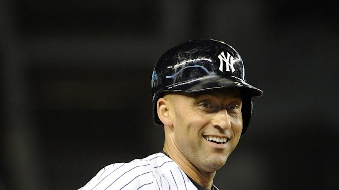 New York Yankees shortstop Derek Jeter smiles on third base in the first inning of a baseball game against the Toronto Blue Jays at Yankee Stadium on Friday, Sept. 19, 2014, in New York. Jeter singled off of Toronto Blue Jays starting pitcher Mark Buehrle and reached third base after Mark Teixeira and Brian McCann were out on a double play. (AP Photo/Kathy Kmonicek)