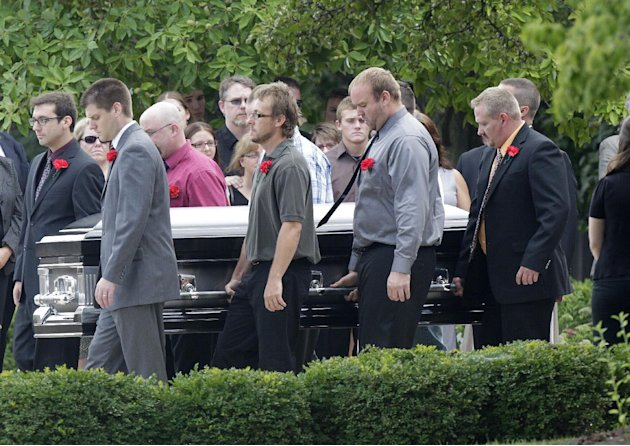 Pallbearers carry Matt McQuinn, killed in the Aurora, Colorado movie theater shooting, from the church after his funeral Saturday, July 28, 2012, in Springfield, Ohio. McQuinn shielded his girlfriend,