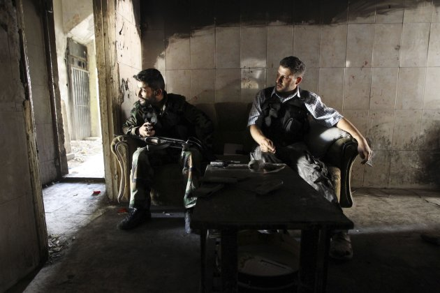 Members of the Free Syrian Army sit on a sofa inside a house in the old city of Aleppo