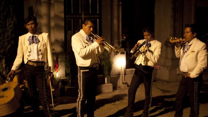A mariachi band performs as they wait for clients at a cemetery during the Day of the Dead celebrations in San Gregorio, Mexico, late Thursday, Nov. 1, 2012. The holiday honors the dead on Nov. 1, coinciding with All Saints Day and All Souls' Day on Nov. 2. (AP Photo/Alexandre Meneghini)