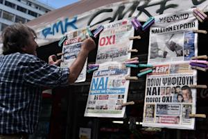 "A man hangs newspapers bearing ""No"" and ""Yes"" …"