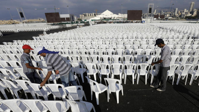 Workers set chairs in preparation of the area where the Pope Benedict XVI will hold a Holy mass on September 16 during his visit to Lebanon, at the waterfront of downtown Beirut, Wednesday Sept. 12, 2012. Pope Benedict XVI travels to Lebanon to encourage his flock in the Middle East. He will also meet with Lebanese authorities as well as Christians from Lebanon and other nearby countries. (AP Photo/Hussein Malla)