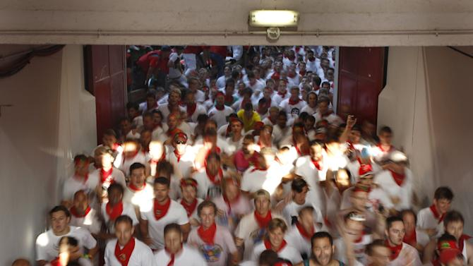 Runners sprint into the bullring during the first running of the bulls of the San Fermin festival in Pamplona