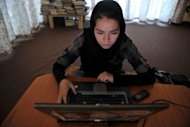 An Afghan ethnic Hazara woman browses the Facebook website on a computer at Kabul&#39;s Young Women For Change, Afghanistan&#39;s first women-only Internet cafe. Afghans are using Twitter and Facebook to bring about social change, particularly women, who are largely marginalised in what is a deeply conservative, male-dominated society