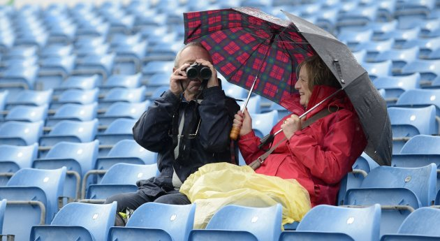 A spectator looks through binoculars as the second test cricket match between England and New Zealand was delayed by rain at Headingley cricket ground in Leeds