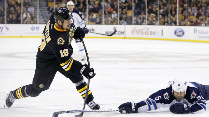 Winnipeg Jets' Mark Stuart (5) tries to block a shot on goal by Boston Bruins' Nathan Horton (18) during the second period of an NHL hockey game in Boston, Monday, Jan. 21, 2013. (AP Photo/Michael Dwyer)