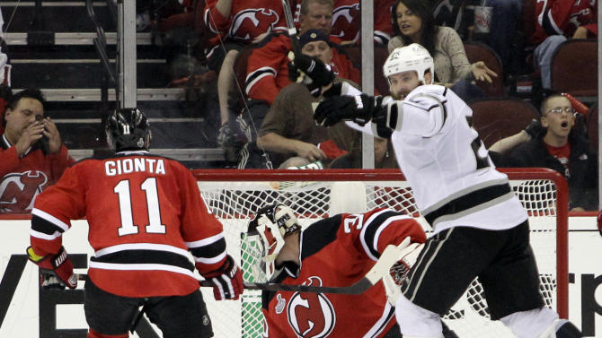 Los Angeles Kings' Dustin Penner, right, celebrates after teammate Jeff Carter scored a goal past New Jersey Devils' Martin Brodeur during the overtime period of Game 2 of the NHL hockey Stanley Cup finals on Saturday, June 2, 2012, in Newark, N.J. Devis' Stephen Gionta, left, looks on. The Kings won the game 2-1.  (AP Photo/Frank Franklin II)