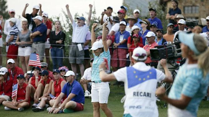 Europe's Karine Icher, of France, celebrates after sinking a 45-foot putt on 18th hole, as members of the U.S. team, left, watch during a four-ball match at the Solheim Cup golf tournament, Saturday, Aug. 17, 2013, in Parker, Colo. (AP Photo/Chris Carlson)