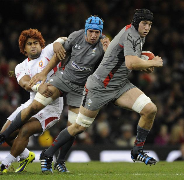 Tonga's Taniela Moa (L) tackles Wales' Justin Tipuric as Ryan Jones (R) makes a break during their international rugby union match at the Millennium Stadium in Cardiff