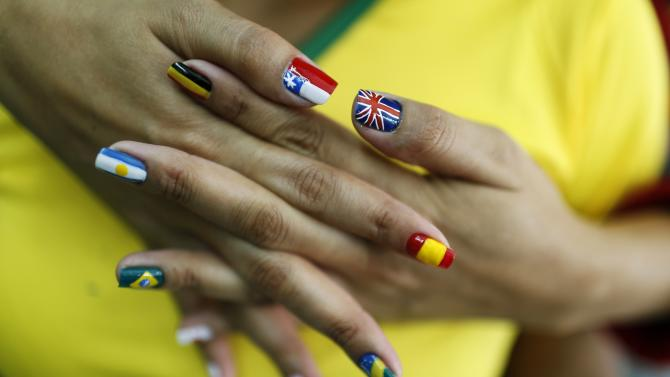 A woman shows her nails after being painted with the flags of countries that will participate in the 2014 World Cup in Rio de Janeiro