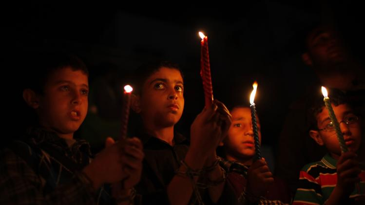 Palestinian boys wearing chains hold candles during a rally marking Palestinian Prisoners' Day in Khan Younis in the southern Gaza Strip
