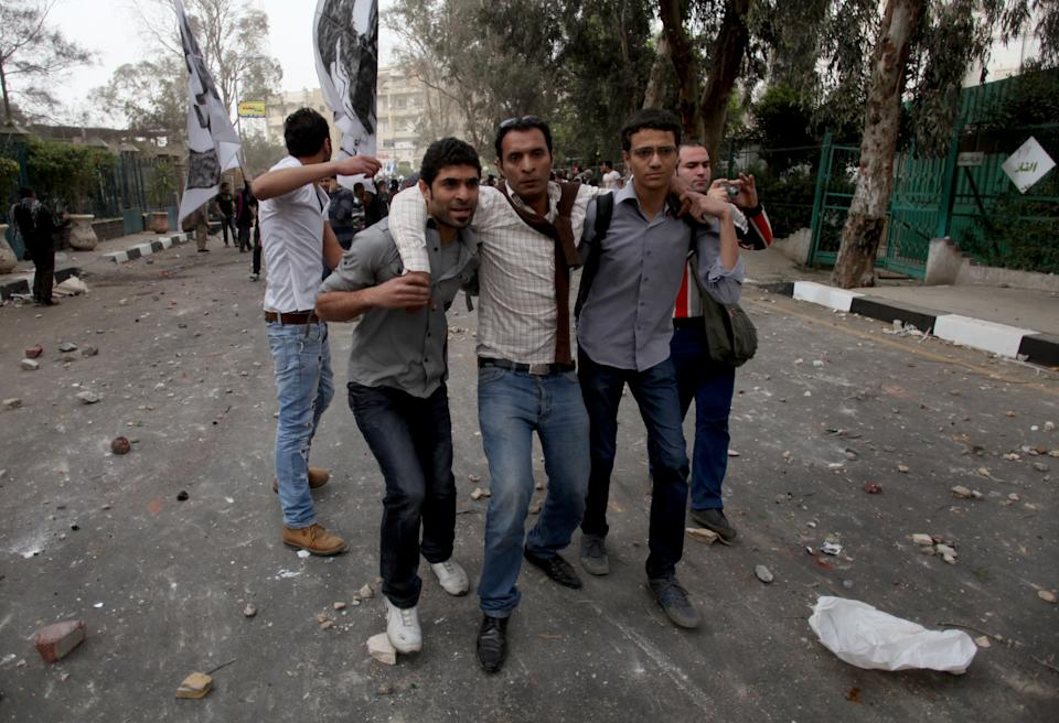 Egyptian protesters assist a wounded comrade during clashes between supporters and opponents and supporters of Egypt's powerful Muslim Brotherhood near the Islamist group's Cairo, Egypt headquarters Friday, March 22, 2013. (AP Photo/Khalil Hamra)