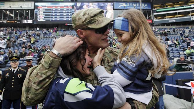 United States Army Sgt. Zach Ames, center, who has been on a one-year deployment to Afghanistan, surprises his wife, Bri Ames, left, and their daughter Emersyn, right, with a reunion prior to an NFL football game between the New York Jets and the Seattle Seahawks on Veterans Day, Sunday, Nov. 11, 2012, in Seattle. (AP Photo/Elaine Thompson)