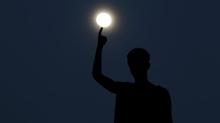 A statue atop a monument representing Cyprus' liberty, seen standing as the moon rises behind, in capital Nicosia, Cyprus, Monday, March 25, 2013. (AP Photo/Petros Giannakouris)