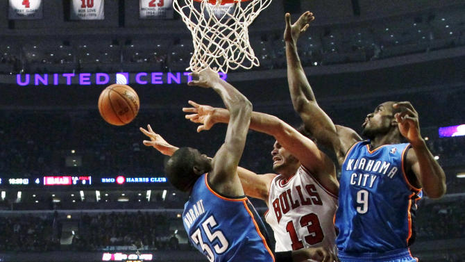 Chicago Bulls center Joakim Noah (13) is forced to pass the ball under the pressure from Oklahoma City Thunder forward Kevin Durant (35) and Serge Ibaka during the first half of an NBA basketball game, Thursday, Nov. 8, 2012, in Chicago. (AP Photo/Charles Rex Arbogast)