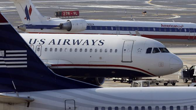 American Airlines and US Airways jets park at gate at the Philadelphia International Airport, Thursday, Feb. 14, 2013, in Philadelphia. The merger of US Airways and American Airlines has given birth to a mega airline with more passengers than any other in the world. (AP Photo/Matt Rourke)
