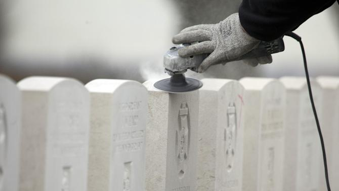 A worker for the Commonwealth War Graves Commission sands down headstones of WWI soldiers at Tyne Cot cemetery in Zonnebeke, Belgium on Monday, April 15, 2013. With nearly 12,000 graves the cemetery is the largest Commonwealth war cemetery in the world in terms of burials. Commonwealth cemeteries and monuments around the world are currently being renovated in preparation for centenary events which begin in 2014. (AP Photo/Virginia Mayo)