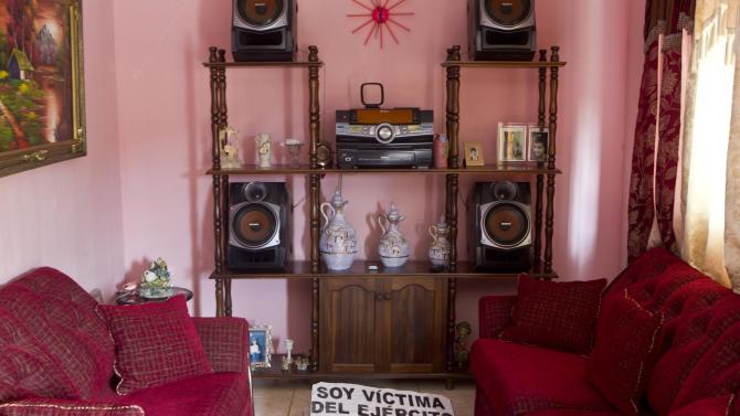 """In this Oct. 18, 2012 photo, a sign with an image of slain Abed Jaasiel Yanez, 15, that reads in Spanish """"I'm a victim of the army,"""" sits on the floor of the living room of his parents' home in Tegucigalpa, Honduras. According to his relatives, Jaasiel  Yanez was killed by soldiers early Sunday, May 27, when he was riding a motorcycle, near a military checkpoint, allegedly accompanied by a young woman.  (AP Photo/Esteban Felix)"""