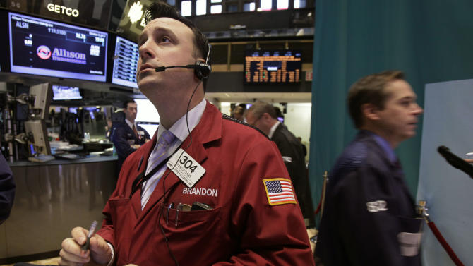 Trader Brandon Barb, left, works on the floor of the New York Stock Exchange Tuesday, Oct. 9, 2012. Another dire prediction about global economic growth is sending stocks lower on Wall Street in early trading. (AP Photo/Richard Drew)
