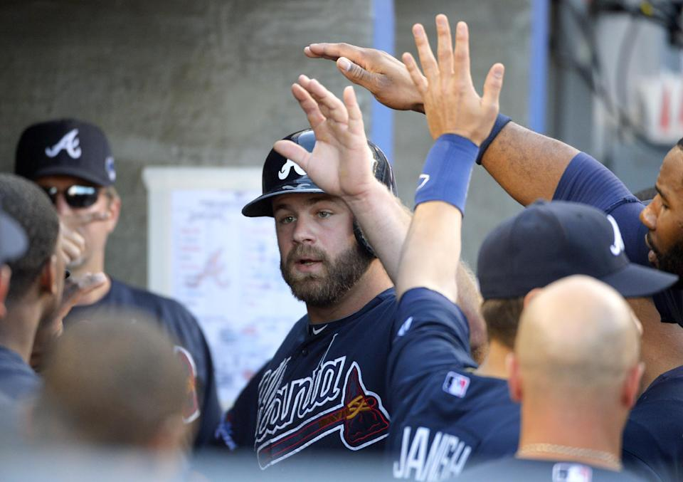 Atlanta Braves' Evan Gattis, center, is greeted in the dugout after he scored on an RBI single hit by Braves' Chris Johnson in the first inning of Game 3 of the National League division baseball series Sunday, Oct. 6, 2013, in Los Angeles. (AP Photo/Mark J. Terrill)