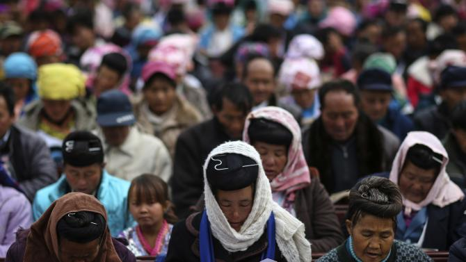 Ethnic Miao people read the Bible at a church ahead of the Christmas week at Xiaoxinzhuang