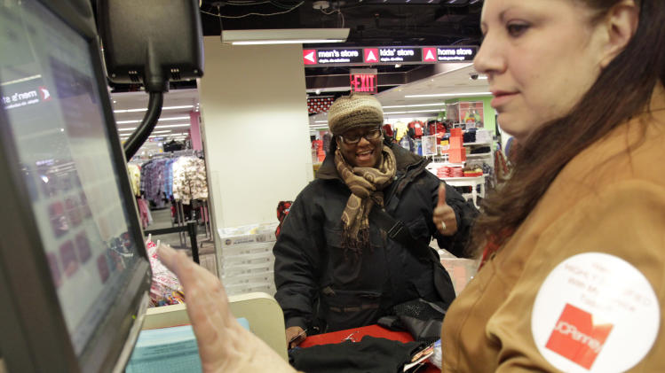 In this Dec. 18,  2010, Maria Johnson Bethune, center, of the Bronx, reacts after the cashier told her how much she saved with coupons and discounts, at the J.C. Penny store at the Manhattan Mall in New York.  Americans spent at a moderate pace last month, giving the economy a boost ahead of the holidays. (AP Photo/Mary Altaffer)