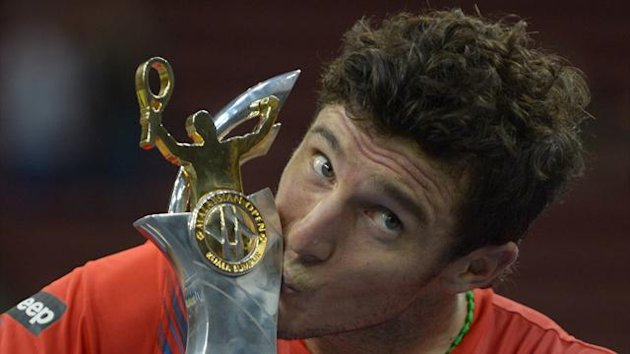 Juan Monaco of Argentina kisses his trophy after winning at the men&#39;s singles final against Julien Benneteau of France at the ATP Malaysia Open