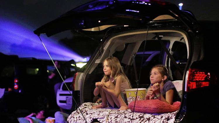 In this July 26, 2013 photo, Maddie Essig, left, age 10, watches a movie with her sister, Claire, age 6, from the tailgate of their parents' car at Bengies Drive-In Theatre in Middle River, Md. The latest threat to the existence of drive-in theaters is the film industry's conversion from 35 mm film to digital prints, and the expense involved in converting projectors to the digital age. (AP Photo/Patrick Semansky)