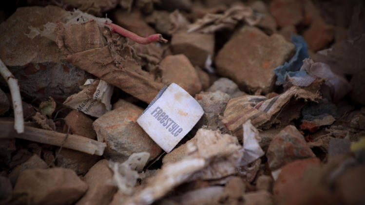 A clothes tag lies in the rubble of a garments factory that collapsed in Savar near Dhaka, Bangladesh, Saturday, May 5, 2013. Officials said Saturday that more than 530 bodies have been pulled from the wreckage of the eight-story Rana Plaza building that collapsed last week, sparking desperate rescue efforts, a national outpouring of grief and violent street protests. (AP Photo/Ismail Ferdous)