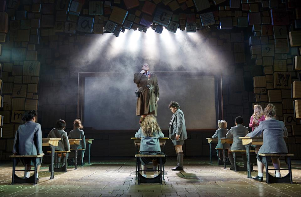 "This theater publicity image released by Boneau/Bryan-Brown shows the cast of ""Matilda The Musical,"" including Bertie Carvel, standing center, during a performance in New York. (AP Photo/Boneau/Bryan-Brown, Joan Marcus)"