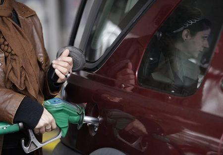 A customer fills her car at a petrol station in south London