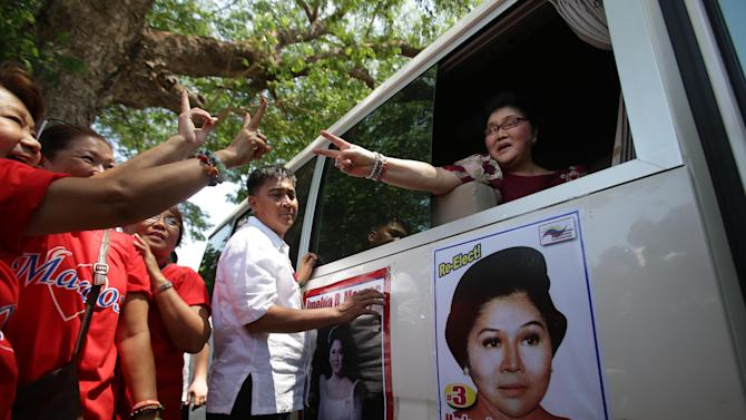 In this May 5, 2013 photo, former Philippine First Lady Imelda Marcos, right, gestures towards her supporters during an electoral campaign in Ilocos Norte province, northern Philippines. Twenty-seven years after her dictator husband was ousted by a public revolt, Imelda Marcos has emerged as the Philippines' ultimate political survivor: She was back on the campaign trail this week, dazzling voters with her bouffant hairstyle, oversized jewelry and big talk in a bid to keep her seat in Congress. (AP Photo/Aaron Favila)