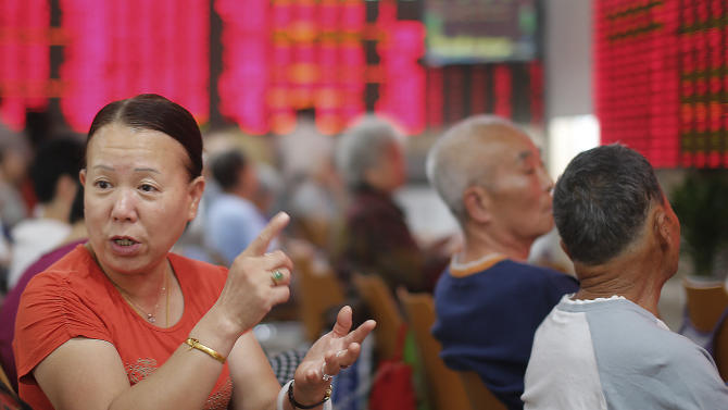 An investor gestures at a private securities company Monday, Aug. 26, 2013 in Shanghai, China. Asian stock markets mostly rose Monday after expectations for an imminent phasing out of the Federal Reserve's monetary stimulus program began to fade. (AP Photo)