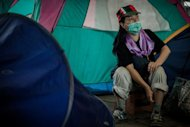 A woman sits at a protesters&#39; camp outside HSBC bank headquarters in Hong Kong on August 13, 2012. he High Court gave the Hong Kong protesters 14 days to leave the courtyard of the bank&#39;s downtown office tower, after which HSBC would be entitled to reclaim the site