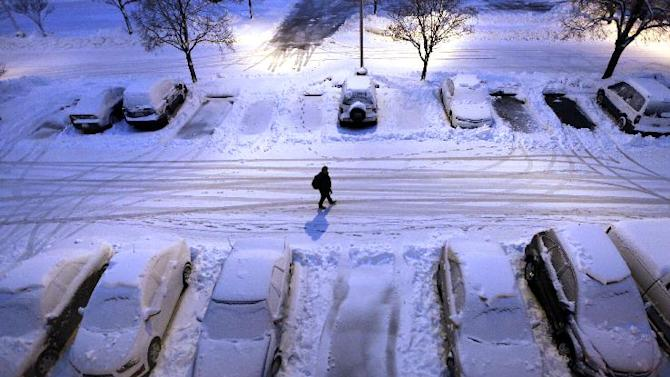 Snow-covered cars in a parking lot greet early morning risers in Madison, Wis. as a severe winter storm moves through the upper Midwest Thursday, Dec. 20, 2012. (AP Photo/Wisconsin State Journal, John Hart)