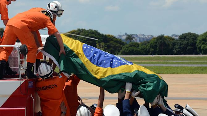 The coffin containing the remains of Brazilian architect Oscar Niemeyer is lowered from a fire truck, in front of the Planalto presidential palace, in Brasilia, Brazil, Thursday, Dec. 6, 2012. Niemeyer, 104, the groundbreaking architect who designed Brazil's futuristic capital and much of the United Nations complex, died Wednesday night in Rio de Janeiro, the seaside city where he was born and where his remains will be buried after he is honored with a service in Brasilia at the presidential palace he designed. (Photo/Cadu Gomes)