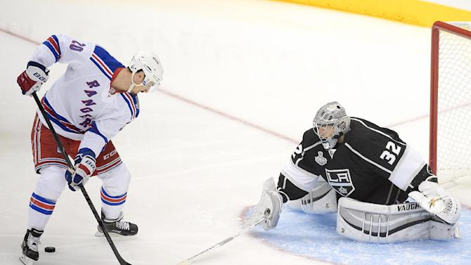 Los Angeles Kings goalie Jonathan Quick, right, blocks a shot by New York Rangers left wing Chris Kreider during the first period in Game 1 of the NHL hockey Stanley Cup Finals, Wednesday, June 4, 2014, in Los Angeles