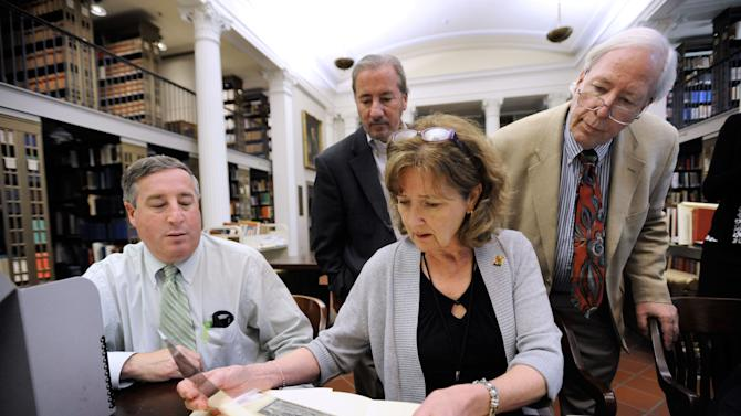 Mitch Yockelson, left, an investigative archivist from the National Archives and Records Administration, C. Dennis Elder, second left, chief financial officer of the Maryland Historical Society, Patricia Dockman Anderson, director of publications and library services at the Maryland Historical Society, and Burton K. Kummerow, right, president and chief executive officer of the Maryland Historical Society, look at stolen historic artifacts as the FBI returns them to the Maryland Historical Society Monday, May 13, 2013 in Baltimore. The documents were stolen from the society by Barry Landau and his assistant Jason Savedoff, who are both in prison for stealing from archives nationwide. (AP Photo/Steve Ruark)