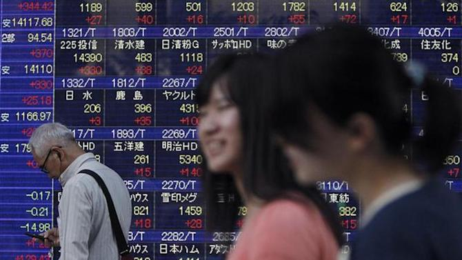 A pedestrian looks at a mobile phone in front of a stock quotation board displaying stock prices outside a brokerage in Tokyo September 9, 2013. REUTERS/Yuya Shino